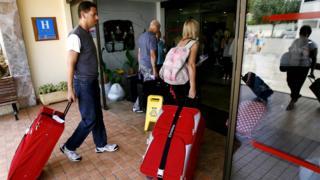 Туристы с чемоданами заходят в отель