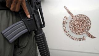 ทหารถือปืนหน้าสัญลักษณ์สำนักงานตำรวจแห่งชาติ
