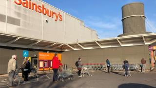 Shoppers observe social distancing as they queue outside Sainsbury's
