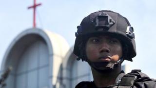 Policajac u Indoneziji stražari pored crkve u Surabaji gde je eksplodirala bomba, Indonezija, 13. maj 2018. godine.