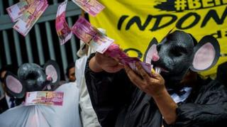 Seorang pengunjuk rasa mengenakan topeng tikus perlambang koruptor