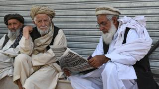 Residents of Quetta in Balochistan sit to read the newspaper.