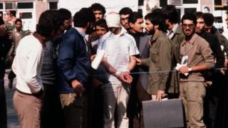 """دیپلمات آمریکا با چشم و دستهای بسته در میان دانشجویان جریان """"پیرو خط امام"""""""