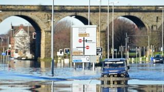A man drives through the flood-waters on Kirkstall Road in central Leeds on December 27