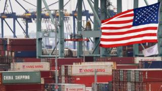 Chinese shipping containers are stored beside a US flag after they were unloaded at the Port of Los Angeles in Long Beach, California on May 14, 2019.