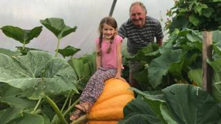 Phillip Vowles and his granddaughter Sophia on top of a giant pumpkin