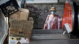 Una mujer con una máscara facial en una escalera mecánica en Belgrado