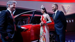 """""""Trên nền cờ đỏ sao vàng, theo sau hai chiếc ô tô là Hoa hậu Việt Nam 2018, trên tay cầm hai lá cờ. Chúng không có biểu tượng Vinfast, lại là cờ đỏ."""""""