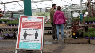 A garden centre with social distancing sign and couple from same household browsing plants