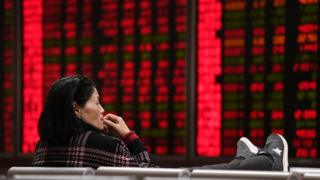 A woman looks at boards showing stock prices at a securities company on the first trading day of the year in Beijing on January 2, 2018