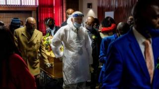 An undertaker wearing a protective suit and a face shield and relatives escort the coffin containing the remains of a COVID-19 (novel coronavirus) victim during a funeral proceeding at a funeral house in Johannesburg, on July 26, 2020. - South Africa has the highest numbers of diagnosed infections in Africa and ranks fifth in the world after the United States, Brazil, India and Russia.