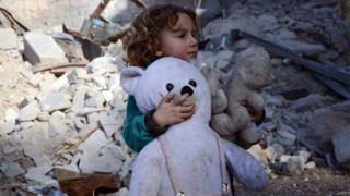 Syrian girl, holding her stuffed toy, stands next to the rubble of buildings in the northwestern Syrian border town of al-Bab on February 25, 2017 after Turkish-backed rebels announced the recapture of the town from the Islamic State (IS) group earlier in the week.
