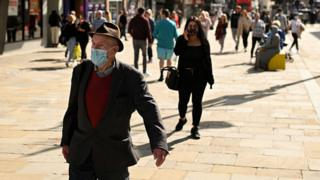 Pedestrians and shoppers, some wearing a face mask or covering walk past shops in Newcastle city centre, north-east England, on 17 September