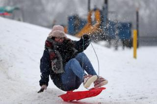 A woman travels on a sled down a slope at Farnborough in Hampshire