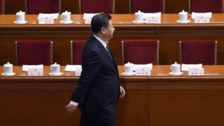 Xi Jinping walking in front of delegates' tables and empty chairs