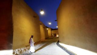 A Saudi Arab walks past renovated buildings in the historic city of Diriyah