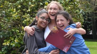 Three students are hugging. One is holding a school folder.