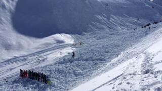 Rescue workers search through the snow brought down by the avalanche