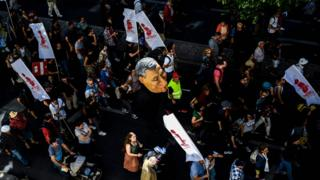Protesters hold a puppet of Portuguese Prime Minister Antonio Costa during a rally in Lisbon