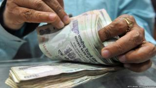 A shopkeeper counts Indian currency notes recieved from a customer at his shop in Mumbai on September 23, 2011