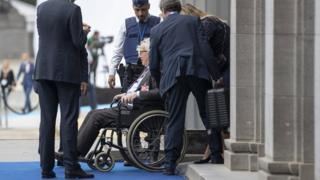 Jean-Claude Juncker is seen seated in a wheelchair as he is brought in through a side entrance of the building