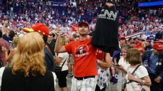 "Trump fan holds up a CNN ""fake news"" shirt"