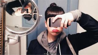 Devojka koja pravi selfi ispred ogledala