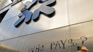 A protestor inscribes the words 'who pays' on to the side of an RBS building.