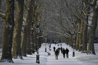 People walk through Green Park after a snow flurry in central London