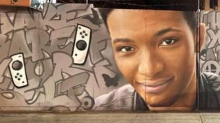 A mural on a wall in New York City. It is graffiti with the face of Etika, a young male. Beside him are two Nintendo Switch controllers