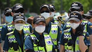 Police officers wearing face masks stand guard during a rally by anti-Trump protesters near the US embassy in Seoul
