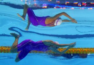 A swimmer in a purple costume is seen underwater. An unusual reflection makes it look like there are two of her.
