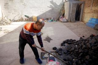 A man shovels coal he uses to heat his home in his courtyard in the village of Heqiaoxiang outside of Baoding, Hebei province, China, December 5, 2017