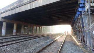 Workmen on train tracks underneath bridge