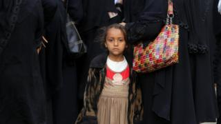 A Yemeni child stands amongst displaced people gathering to register at an evacuation centre after fleeing home due to ongoing conflict, in Sana'a, Yemen, 17 November 2018