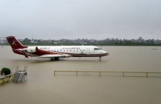 An aircraft is seen parked on the flooded apron of Biratnagar's domestic airport after heavy rains in Biratnagar, some 240km from Nepal's capital Kathmandu, on August 12, 2017.