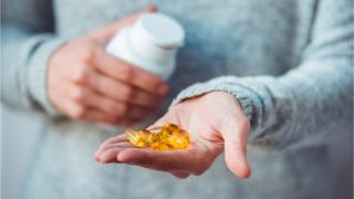 Fish oil supplements in a woman's hand