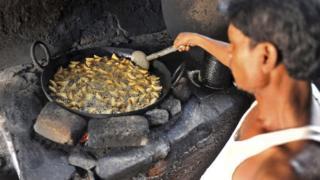 An Indian worker fries samosas
