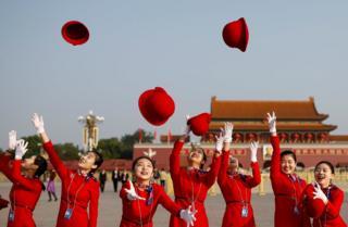 Secretarias del gobierno lanzan sus sombreros en el aire mientras posan para los fotógrafos en la Plaza Tiananmen.