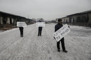 Migrants hold placards during a protest outside a derelict customs warehouse in Belgrade, Serbia