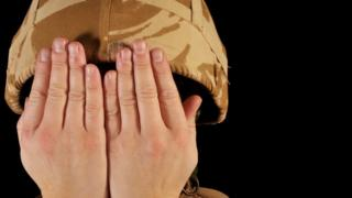 Soldier with hands over face