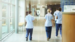 A group of four young trainee nurses including male and female nurses, walk away from camera down a hospital corridor. They are wearing UK nurse uniforms of trousers and tunics.