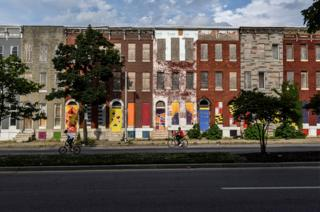Young boys ride their bikes past a boarded-up and abandoned row of houses in Baltimore.