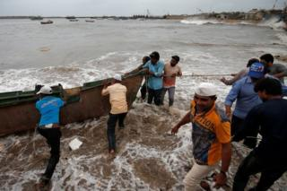 Fishermen move a fishing boat to a safer place along the shore ahead of the expected landfall of Cyclone Vayu at Veraval, India, June 12, 2019