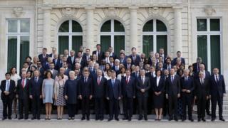 Autoridades reunidas no encontro da OCDE posam para foto em escadaria em frente a um prédio