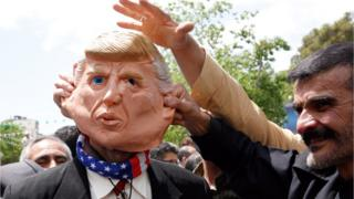Demonstrators stand around an Iranian man that wears a mask of the US President Donald J. Trump during an anti-US rally, to show their support of Iran's decision to pull out from some part of nuclear deal, in Tehran, Iran, 10 May 2019.