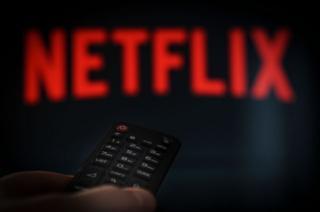 Un control de tv ante un letrero de Netflix