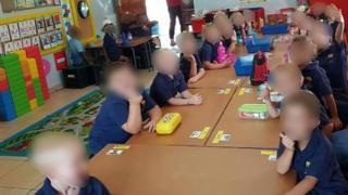White schoolchildren sit apart from black school children in the same classroom