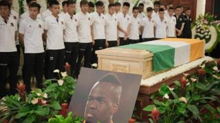 "Beijing Enterprises club football players look at the coffin of Cheick Tiote during a memorial service in Beijing on June 13, 2017. Tiote, who was a member of the Ivory Coast squad that ended a 23-year drought to win the 2015 Africa Cup of Nations, died on June 5, 2017 after ""suddenly fainting"" during a training session with his second tier Chinese club Beijing Enterprises."
