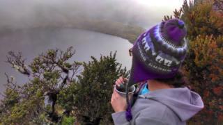 Mujer toma café frente a una laguna en lo alto de una montaña. (Foto: Liliana X. González)